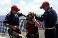 US Navy 080923-N-9758L-312 Chief Damage Controlman Donald Grother and Chief Damage Controlman Thomas Thompson help the son of a Sailor don fire-fighting equipment during a friends and family day cruise.jpg