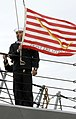 US Navy 090401-N-5033P-047 A Sailor aboard the guided-missile destroyer USS Ramage (DDG 61) prepares to shift colors as the ship pulls into port after a seven-month deployment.jpg
