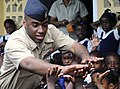 US Navy 100512-N-4971L-232 A Sailor plays with children during a Project Handclasp donation.jpg