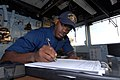 US Navy 111105-N-DU438-039 Quartermaster 3rd Class Brandon Shannon writes an entry into the ship's deck log during a quartermaster watch.jpg