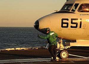 US Navy 111213-N-RB391-089 A Sailor guides an E-2C Hawkeye aboard the aircraft carrier USS Enterprise (CVN 65).jpg