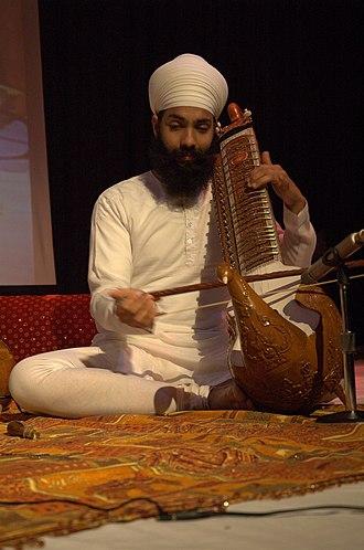 Taus (instrument) - A Sikh man playing the Taus
