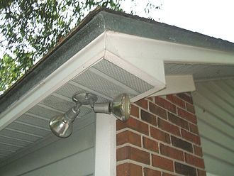 Soffit - Soffit lining a house in Northern Florida, United States. In this example the soffit is 12 inches wide and made from center lanced U groove perforated sections of vinyl in a return fashion and fixed to a truss roofing system.