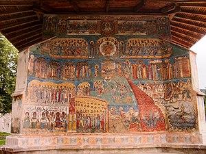 Le jugement dernier, peinture en style orthodoxe byzantin sur les murs de la monastères Voroneţ construite en 1488 en Roumanie. On y voit a gauche le paradis avec les saints et l'Arbre de la Vie, à droite les enfers avec des démons et le feu qui descend dans les abysses et en haut l'image contemplative du Christ tout puissant. À droite et à gauche du Christ, on voit les signes du zodiaque .