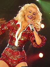 A blonde woman in a sparkling red bodysuit singing happily to a microphone