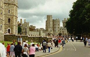 Ein Foto eines grauen Steinschlosses, das sich links neben dem Bild erstreckt.  Das Zentrum bildet eine Straße, auf der viele Menschen laufen.