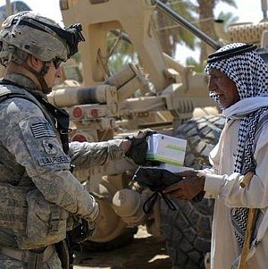 "14th Infantry Regiment (United States) - A 2-14 Soldier providing medical supplies to Iraqi citizen, during Operation ""Outreach,"" a  humanitarian aid mission near Baghdad, Iraq, 2010"