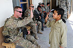 82nd Airborne Division medic high-fives Afghan boy DVIDS483321.jpg