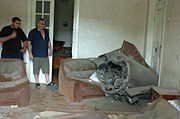 Two men looking at a missile lying across a sofa