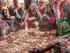Afghan rug - Afghan women from the western part of the country showing traditional Adraskan Afghan carpets.