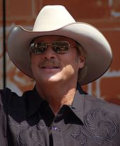 A fair-haired man wearing dark glasses and a white cowboy hat