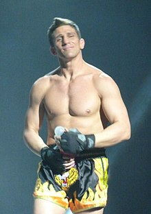 A muscled man poses on stage.