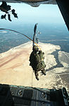 An Air Force Air Liaison Officer (ALO) jumps out of a C-130 Hercules aircraft during a training exercise with members of the 82nd Airborne Division DF-ST-84-06278.jpg