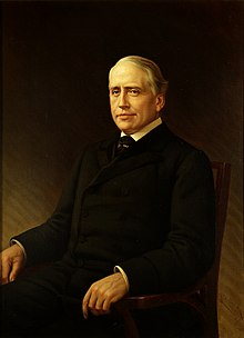 oil on canvas portrait of a silver and gray-haired Senator Gorman, wearing a dark suit and seated toward the left against a dark background, facing the viewer with a soft smile on his lips