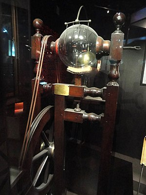 Franklin's electrostatic machine -  The glass globe spinning against the bottom pad develops static charge, which is conducted away by metal needles at top.