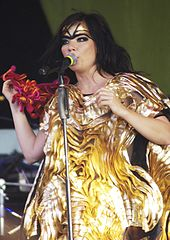 A picture of a woman dressed in yellow singing