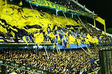 Photographie en couleurs. Dans les tribunes d'un stade, de nombreux supporters agitent des banderoles de couleur jaune et bleue.
