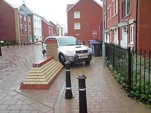 Overspill parking - Bollards and brick pillar in a housing area with car parked diagonally onto the footway