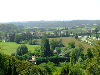 Photo overlooks the countryside on the west side of the Mincio near Borghetto. The old bridge is at the left and the Mincio loops from there to the right foreground amid trees.