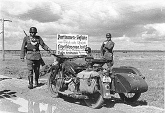 "Feldgendarmerie - Feldgendarmerie operating in occupied Russia, July 1941. The sign says ""Partisan danger ahead. Single vehicles Stop! Hold weapons ready.""."