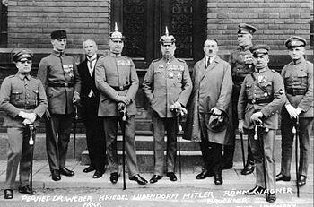 Photo noir et blanc de neuf hommes debout, dans une rue, devant la porte d'entrée fermée d'un bâtiment. Sept hommes sont en tenue militaire. Il s'agit d'Adolf Hitler et des autres personnalités inculpées lors du son procès en 1924.
