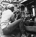 COLLECTIE TROPENMUSEUM Een assistent boormeester werkt aan de dieselmotor van een boormachine TMnr 20007997.jpg
