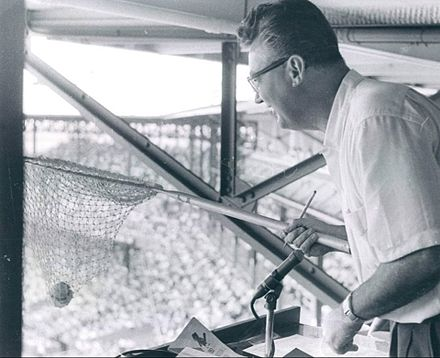 Caray using his net to catch a foul ball in the Cardinals broadcast booth, 1957. He continued this practice when he worked for other teams. Caray and net 1957.JPG