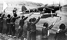 Chiran high school girls wave farewell with cherry blossom branches to departing kamikaze pilot in a Ki-43-II Hayabusa.