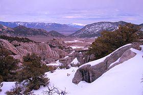 Foto prenita de la Grandurbo de Rokoj Nacia Rezervo kun la Black Pine Mountains en la fono kaj kovrita en neĝo