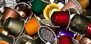 Single-serve coffee container - Used Nespresso coffee capsules, showing the puncture holes in the top and bottom for mixing the product with water
