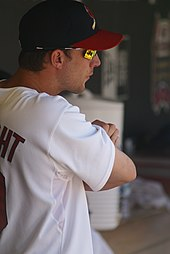 A man in a white baseball jersey, navy blue baseball cap with a red brim, and orange mirrored sunglasses stands with his arms crossed.