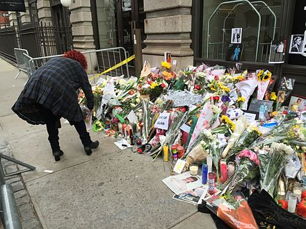 A woman places flowers outside Bowie's apartment in New York on Lafayette Street the day after his death was announced. David Bowie Death New York Apartment Memorial 2016 7.JPG