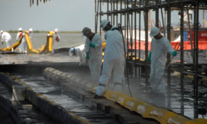 Health consequences of the Deepwater Horizon oil spill - Workers performing decontamination of containment booms used during the Deepwater Horizon oil spill.