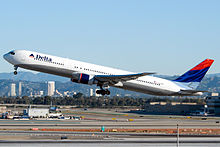 A Delta Air Lines 767-400ER taking off with airport runways and taxiways in view in the background.