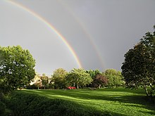 double rainbow over green in bright sunshine with large tree on both left and right of image