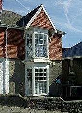 Sur une rue de colline se dresse une maison jumelée de deux étages avec des baies vitrées à l'avant et un toit en tuiles en pente avec une cheminée.