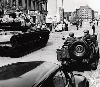 Berlin Crisis of 1961 - American tanks face an East German water cannon at Checkpoint Charlie.