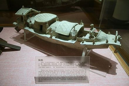 An Eastern Han (25–220 AD) Chinese pottery boat fit for riverine and maritime sea travel, with an anchor at the bow, a steering rudder at the stern, roofed compartments with windows and doors, and miniature sailors. - Rudder