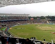 View of a grassy cricket pitch from the stands