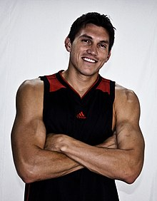 A muscular man wearing a black tanktop with red on the shoulder straps which his arms crossed over his upper abdomen.
