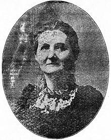 Een krantenbeeld van een blanke vrouw van middelbare leeftijd, in een ovale lijst.