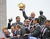 Photograph of nine members of the England rugby team on an open top bus victory parade. Lawrence Dallaglio is in the centre holding up the golden coloured Webb Ellis Cup, which is the trophy awarded to the winners.