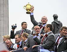 White men in grey suits, pale blue shirts and red ties celebrate upon the top floor of an open-top bus. On man holds the golden trophy in the air with one hand.