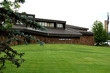 Building, with grass lawn and tree in foreground