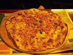 photographie d'une tarte flambée alsacienne à la crème, oignons et lardons