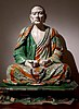 seated Buddhist monk in coloured pottery