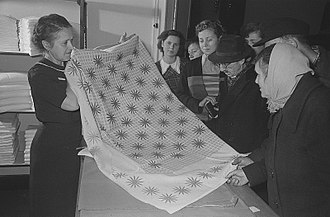 Napery - A shopkeeper shows a tablecloth to customers in Leipzig, November 1953