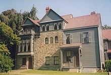 Une grande maison de trois étages en bois et en pierre