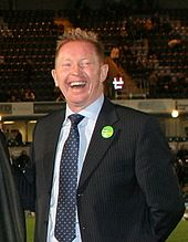 A laughing Caucasian man in a black suit with short blonde hair.