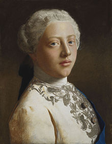 Head-and-shoulders portrait of a young clean-shaven George wearing a finely-embroidered jacket, the blue sash of the Order of the Garter, and a powdered wig.